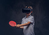 Little redhead boy dressed in a white t-shirt playing ping-pong with a virtual reality glasses. Isolated on dark textured background.