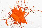 Blot and splashes of orange paint