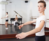 Slim young man rehearsing ballet dance in studio