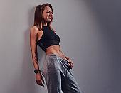 Fashion, sport, health. Slim fitness girl wearing sportswear leaning on a wall in a studio.