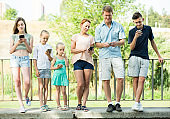 Portrait of active large family standing with their mobile phones outdoors