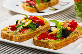 Bread with guacamole, canned tuna, cheese, vegetables