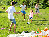 Parents with children playing football