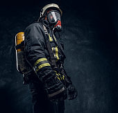 Firefighter in safety helmet and oxygen mask wearing protective clothes.