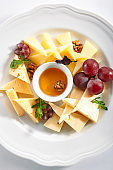 Cheese Platter with Honey, Nuts and Grapes on White Restaurant Plate