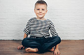 Cute little boy sitting on floor and smiling.