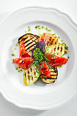 White Restaurant Plate of Grilled Vegetables and Fresh Greens Isolated