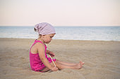 Little girl in kerchief plays in the sand on the sea in summer