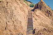 Wooden staircase attached to a clay rock on a sunny day