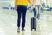 A girl walks through the airport hall and carries a suitcase on wheels. Vacation travel