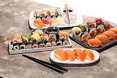 close up of sashimi sushi set with chopsticks and soy - sushi roll with salmon and sushi roll with smoked eel