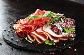 Marble cutting board with prosciutto, bacon, salami and sausages on wooden background. Rustic Meat platter