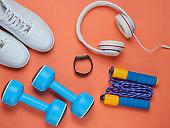 Dumbbells, smart bracelet, headphones, sneakers, jump rope on coral color background. Minimalistic sport concept. Top view.