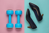 Leddy's sport. Women's high heel shoes with dumbbells on pastel background. Fitness and fashion concept. Top view, minimalism