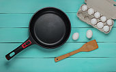 Non-stick pan, tray of eggs, cooking spatula on blue wooden background. Top view