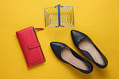 Shopping concept. Fashion studio shot. Women's high-heeled shoes, shopping basket, wallet on yellow background. Top view