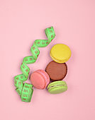Colored macaroons cookies and ruler on a pink pastel background. The concept of losing weight. Top view.