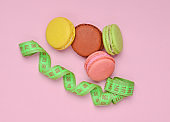 Colored macaroons cookies and ruler on a pink pastel background. The concept of losing weight. Top view