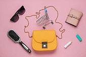 What's in the bag? Women's accessories, shoes on pink pastel background. Beauty and fashion concept. Top view, flat lay minimalism