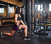 Young brunette fit woman execute exercise with exercise machine Cable Crossover in gym.  Workout process