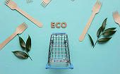 Eco-vegetarian shopping. Shopping trolley, wooden forks, green leaves on blue pastel background. Top view