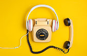 Retro style creative flat lay. Rotary vintage telephone with classic white earphones on a yellow background. Pop culture. Top view