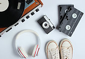 Flat lay retro 80s pop culture objects. Vinyl player, headphones, video tapes, film camera, sneakers on white background. Top view