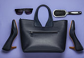 Flat lay style women's clothing, accessories on purple background. Bag, leather high heel shoes, sunglasses, comb. Top view