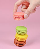 Female hand lowers the pink macaroons cookies. A stack of macaroons on a pink pastel background. Minimalism