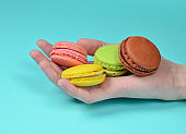 Colored macaroons in hand close-up on a blue background