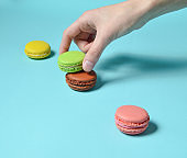 Female hand lowers the green macaroons cookies. A stack of colored macaroons on a blue pastel background. Minimalism
