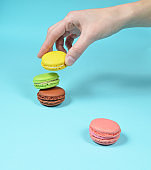 Female hand lowers the yellow macaroons cookies. A stack of colored macaroons on a blue pastel background. Minimalism