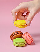 Female hand lowers the yellow macaroons cookies. Many macaroons on a pink pastel background. Minimalism