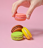 Female hand lowers the pink macaroons cookies. Many macaroons on a pink pastel background. Minimalism