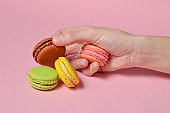 Colored macaroons in hand close-up on a pink background