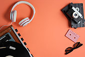 Flat lay retro 80s pop culture objects. Vinyl player, headphones, audio cassette, video tapes, film camera on coral color background. Copy space. Top view