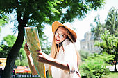 Tourism concept, travel to new cities. Attractive female tourist in a felt hat enjoys city map and talking on the phone.