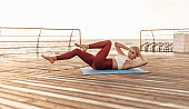 Morning exercise. Young sport woman in sportswear is practicing double twisting exercise lying on seaside promenade. Abs training