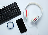 Modern digital gadgets and accessories. Laptop, smartphone, smart bracelet, headphones on white background. Top view.