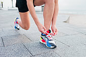 Fit woman in sportswear tying shoelace of sports shoes on a concrete tile and preparing to run on a city beach