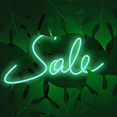 Sale banner with tropical leaves on night sky. Neon bright illustration with flashlight on dark green background.