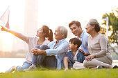 three generation asian family sitting on ground watching sunset