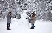 Friends building snowman