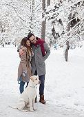 Couple walking dog on snow