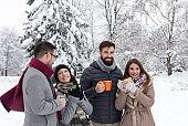 Friends drinking tea on snow