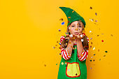 Little girl in elf costume blowing colorful confetti