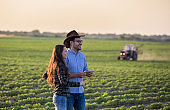 Man and woman farmers in front of tractor in field