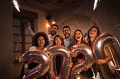 People having fun at New Years party, waving with sparklers and holding 2020 balloons