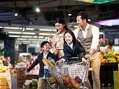 happy asian family shopping in supermarket