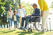 asian parents and son visiting grandparents in nursing home